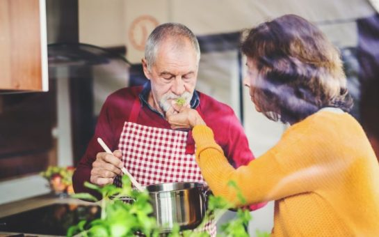 A man in a red jumper and red apron cooking. He is holding a wooden spoon in a silver sauce pan. A lady with short brown hair in an orange cardigan is holding some green herbs for him to smell. There are also some blurred green herbs in the foreground.
