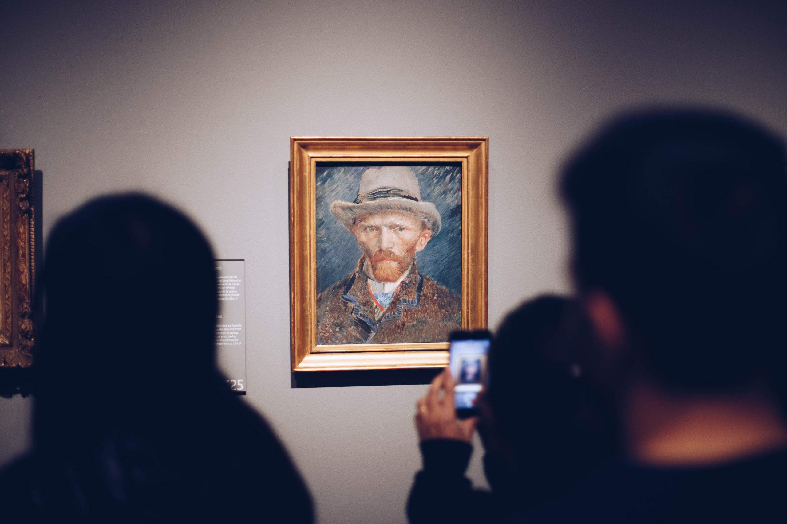 Image of a Van Gogh portrait on a wall, whilst in the foreground people are looking at it, one person taking a photo on their phone.