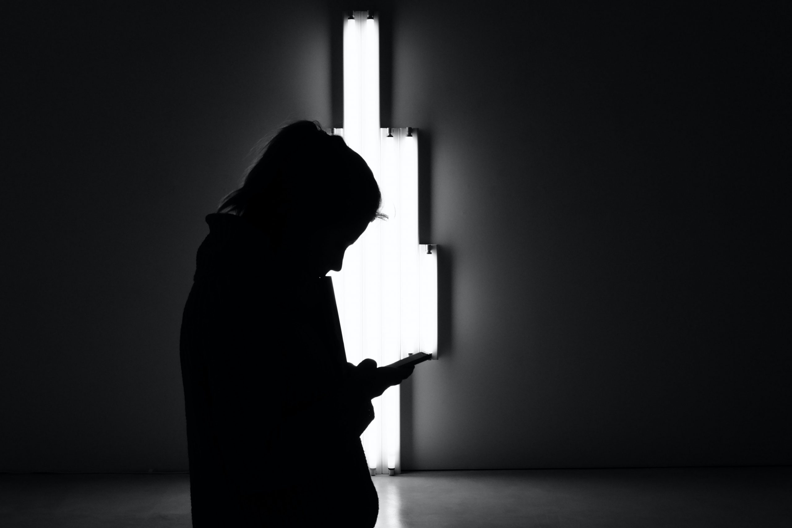 A silhouetted girl looks at her phone against a light installation.
