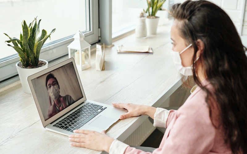 A woman video calls a man - both are wearing face masks