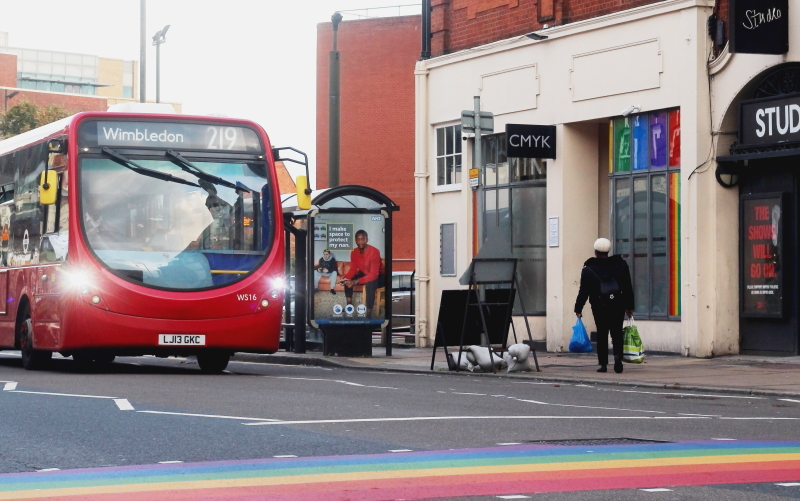 A bus to Wimbledon stopped outside of Bar CMYK and the LGBT+ rainbow crossing.