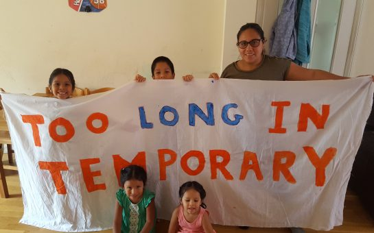 Janeth and her family hold a banner reading 'Too Long in Temporary'.