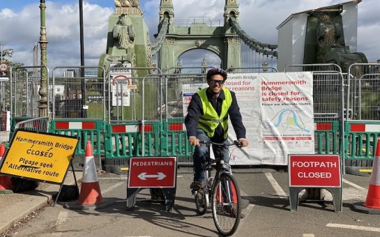 Robert Osterbauer in front of the closed Hammersmith Bridge on his bicycle, surrounded by 'bridge closed' signs.