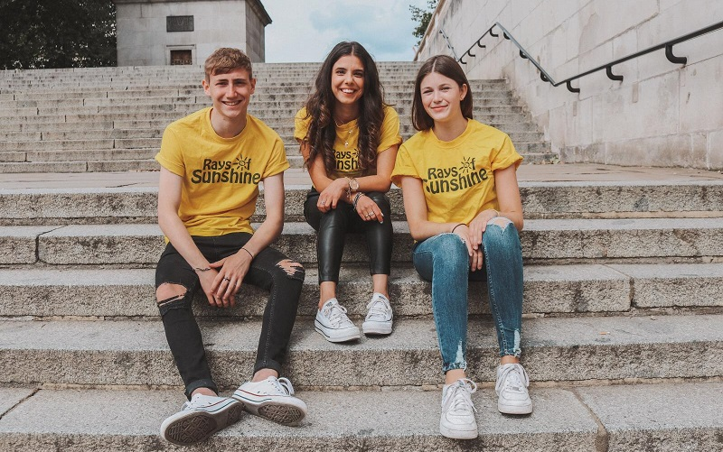 Three Ray of Sunshine Kilimanjaro climbers sat on steps