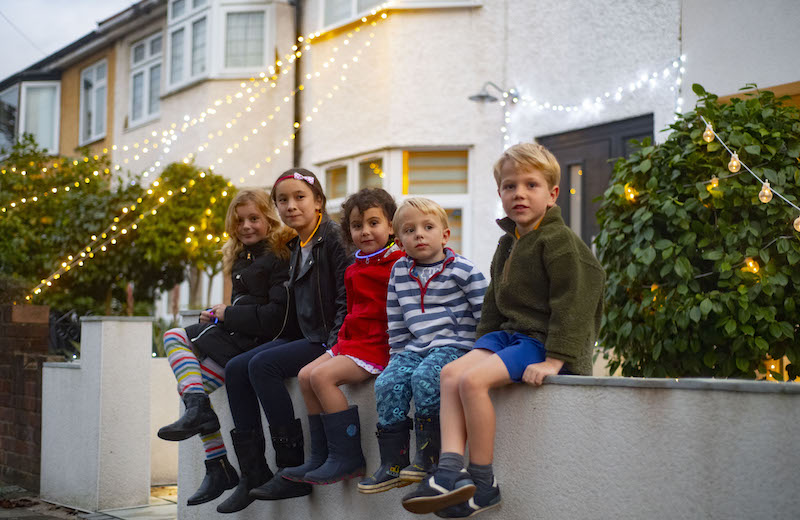 Children sitting on wall in front of fairy lights