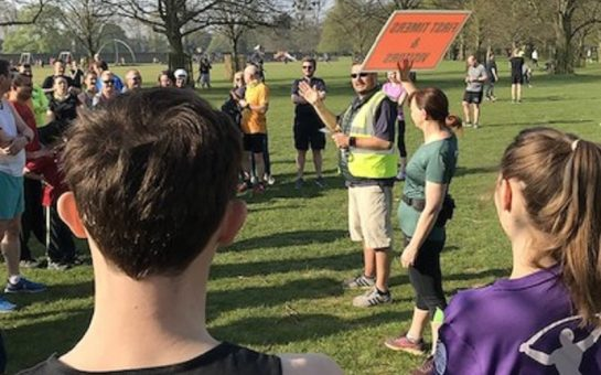 parkrun volunteer holding sign among people