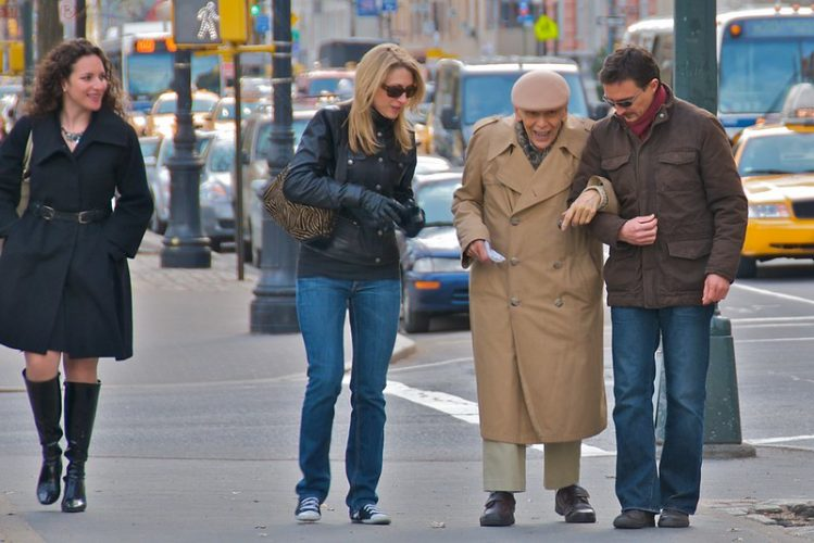 Two people helping an elderly man down the street