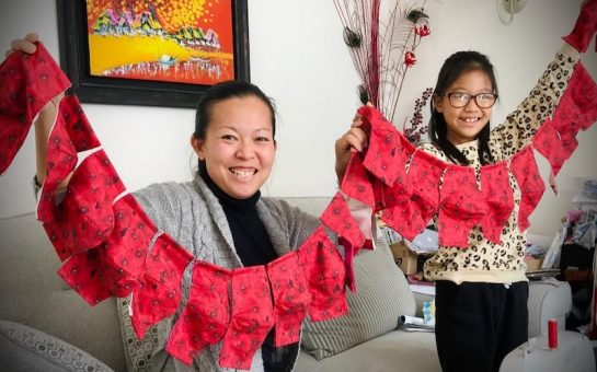 Mum and daughter hold poppy face masks