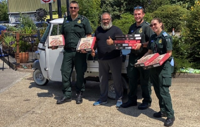 Peppe and ambulance workers holding pizzas outside