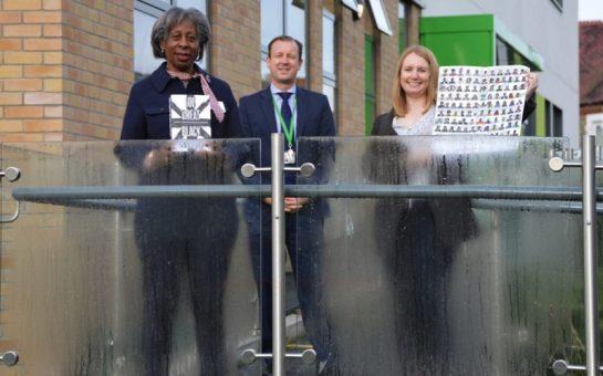 Yvonne Davis presents black history book and poster to Balham Head-Teacher Christian Kingsley alongside donator Carly Lewis