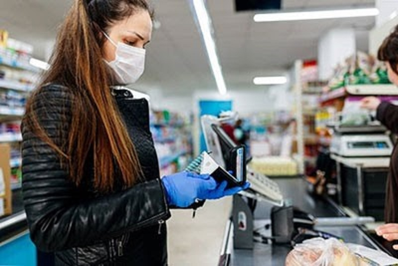 person stands at the checkout in a supermarket