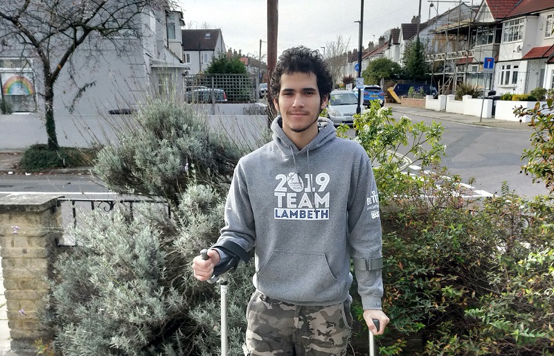 jonnas guerra with his crutches in front of his house