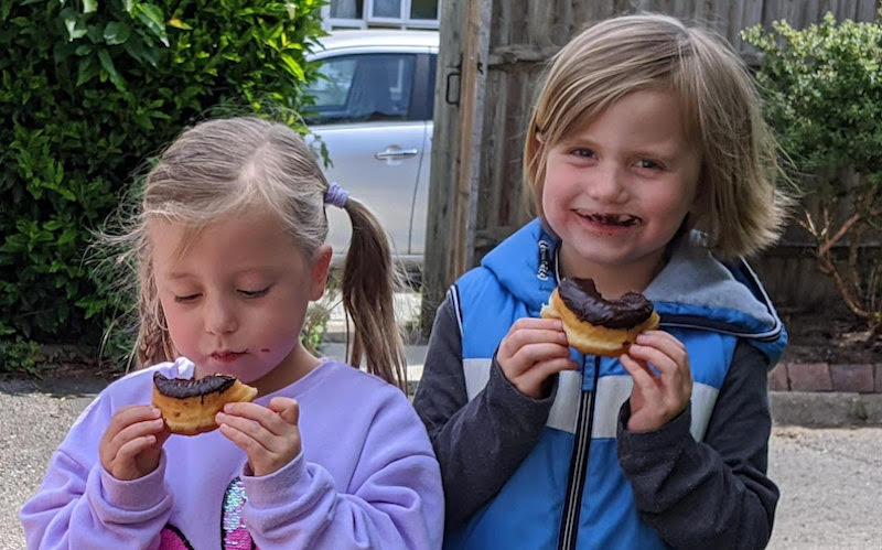 A picture of happy children eating doughnuts