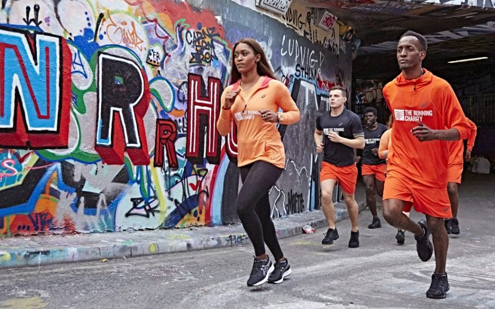 People jog past a wall covered in graffiti wearing orange t-shirts which have the running charity logo on them