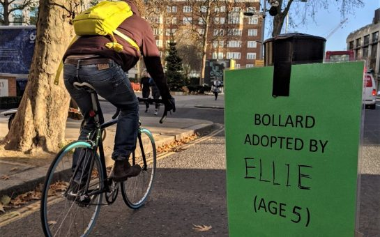 "A bollard with a sign: ""Bollard adopted by Ellie (Age 5)"". A cyclist rides in the background."