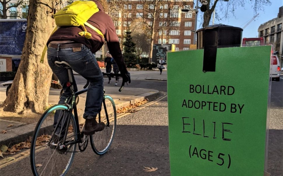 """A bollard with a sign: """"Bollard adopted by Ellie (Age 5)"""". A cyclist rides in the background."""