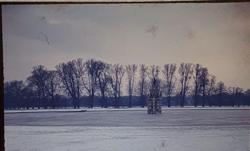 A snowy scene featuring the lake and Diana statues in bushy park