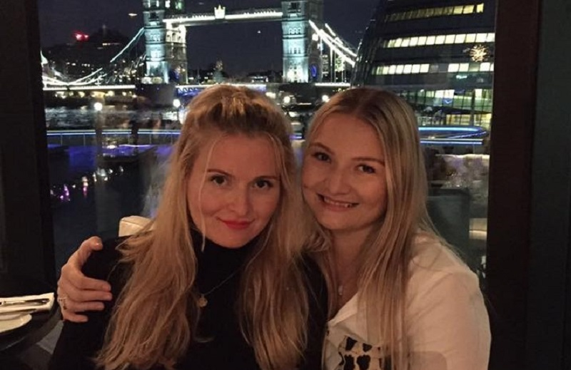 Sam and Charlotte Crilly have their arms round each other and are smiling at the camera with Tower Bridge in the background.