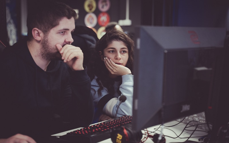 A man and Lily Jahan sit in front of a computer monitor in the esports arena looking at it intently