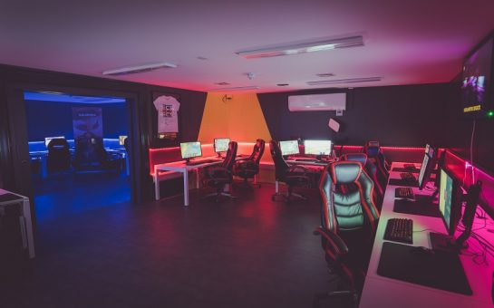 A photo of the Roehampton University Esports Arena. Several gaming PCs and chairs are around the room