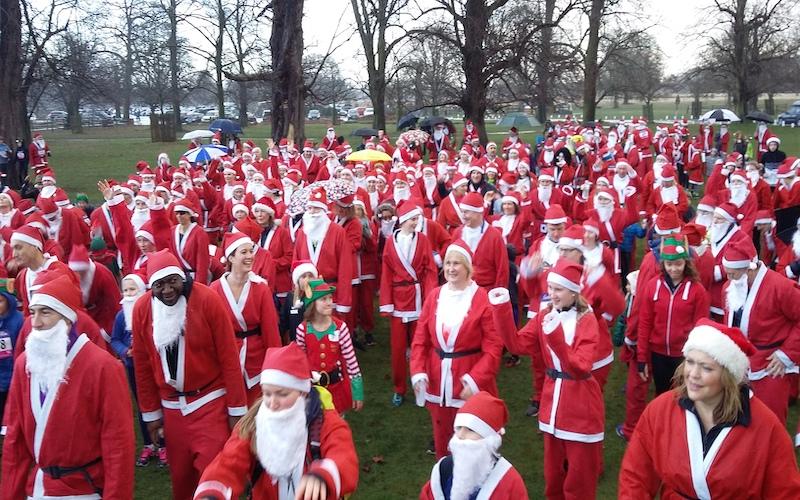 Hundreds of runners dressed in Santa costumes in Bushy Park for 2019 fun run.