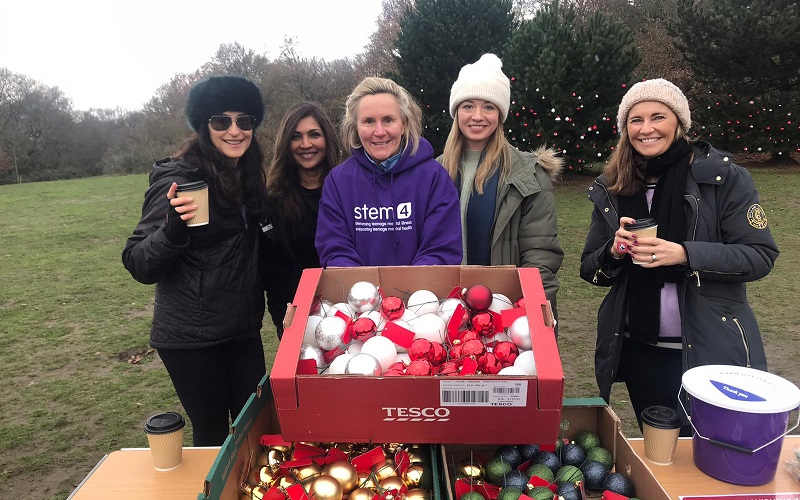 volunteers pictured with baubles in front of trees in Wimbledon Common