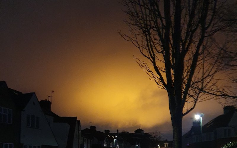 orange glow in sky over houses in Twickenham