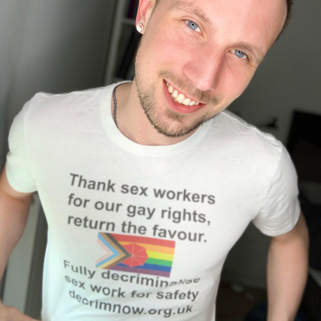"""Jason Domino smiles. He wears a t-shirt: """"Thank sex workers for our gay rights, return the favour"""""""
