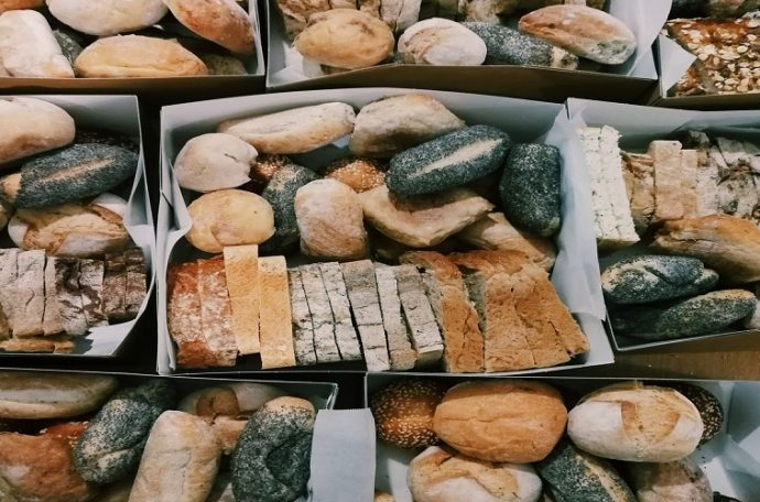Hampers of various types of bread, including poppy seed rolls and slices of different loaves