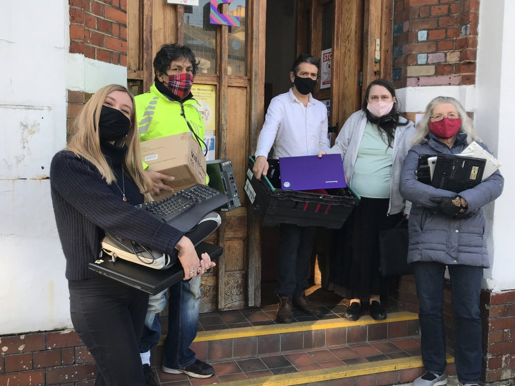 Members of Lambeth TechAid holding computers