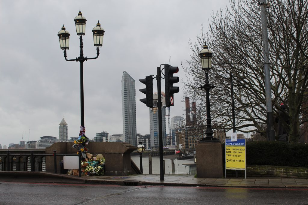 Picture of the site of the fatal collision on Battersea Bridge, showing flowers around a lamppost and a police sign calling for witnesses to the accident.