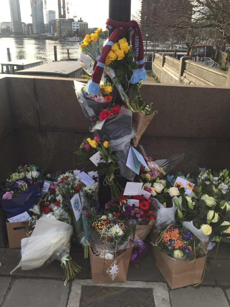An image of flower tributes tied to a lamppost that were left for Mr Ryan on Battersea Bridge.
