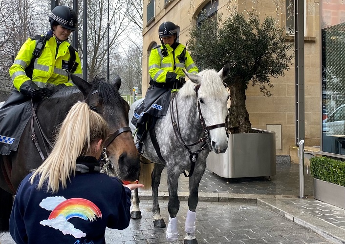 two mounted police officers on horses, one being fed an apple at the Berkeley Hotel