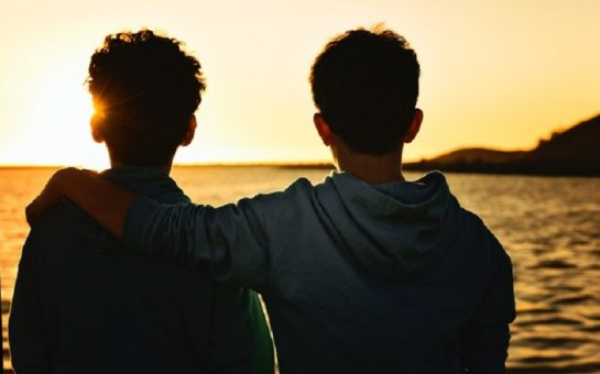 two boys sat by the sea as the sun sets