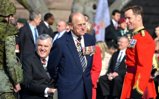 Prince Philip in a military uniform in the centre of the image smiling at another uniformed officer.
