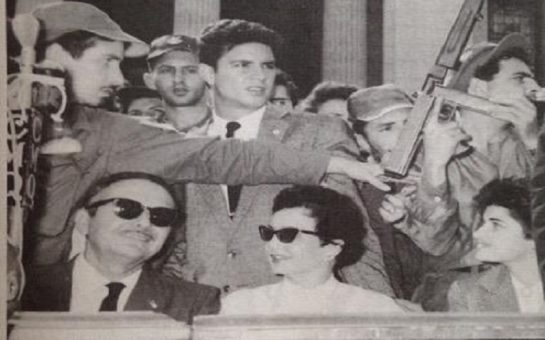 Picture of Helen's great aunt Ellie in Cuba, wearing sunglasses, in a crowd of people with a man holding a gun