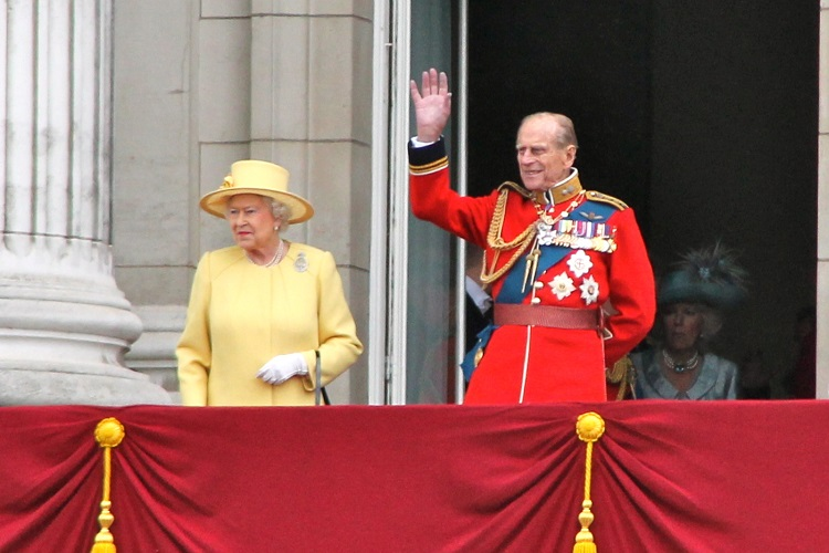 The queen in yelloe and prince philip in a military uniform waving from the balcony at buckingham palace