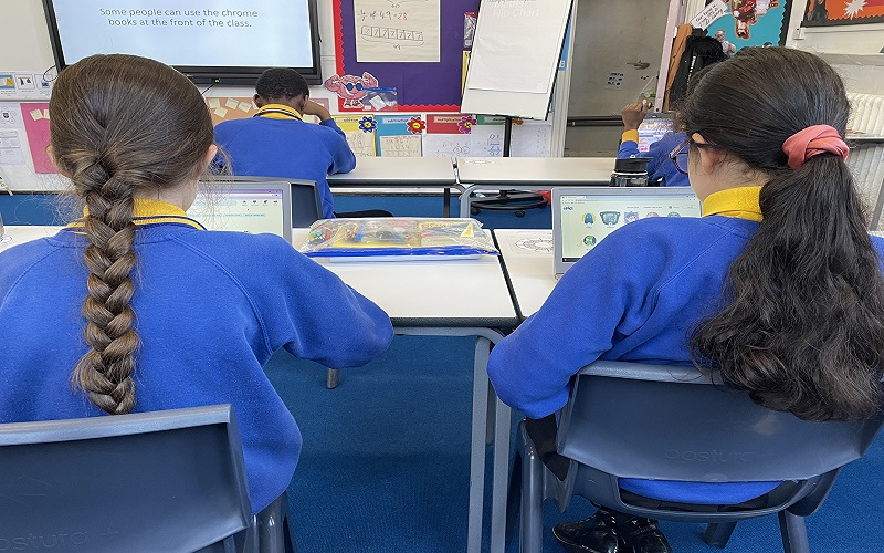 Two school pupils in blue and yellow uniform learning on laptops.