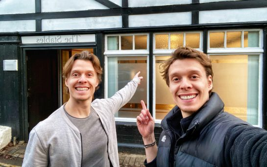 twins stand in front of new studio space, smiling