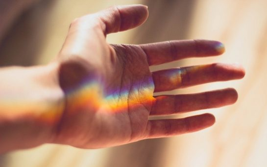 A hand with a rainbow light shining over it.