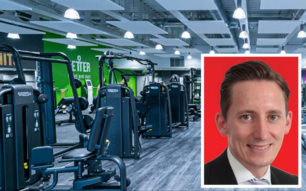 """In the background, a very polished new leisure centre is flanked by a green wall: """"Better"""". A smiling man appears in the bottom right corner - Cllr Oliver Lewis."""