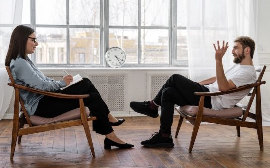 An image of a man and woman sitting across from each other as if she is taking notes like a drug and alcohol service therapist during Covid