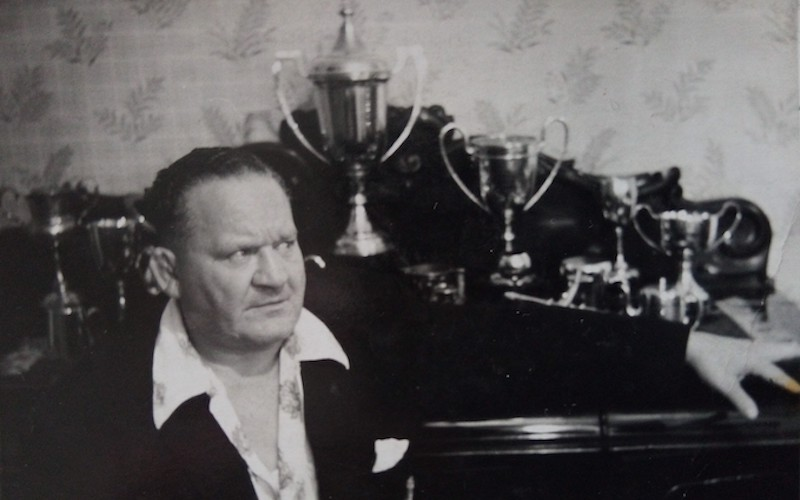 wrestler chick knight sits in front of his trophy collection