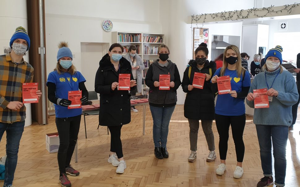 AFC Wimbledon fan volunteers with COVID test leaflefts