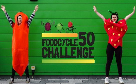 "Two women, one dressed as a carrot, the other dressed as a strawberry, standing in front of a green wall with the words ""FoodCycle 50 challenge"" written on it."