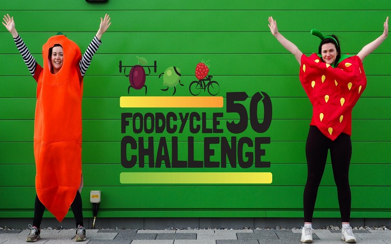 """Two women, one dressed as a carrot, the other dressed as a strawberry, standing in front of a green wall with the words """"FoodCycle 50 challenge"""" written on it."""