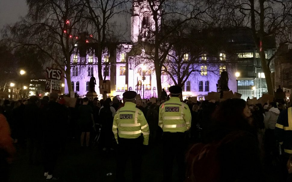 A large group of people at the #KillTheBill protest with two policemen in fluorescent yellow jackets in the foreground