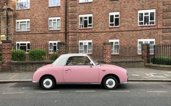 A pink car parked on a road outside a block of flats.