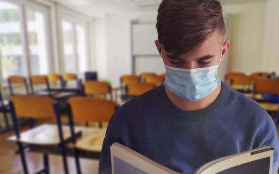 male student wearing face mask in school classroom reading textbook