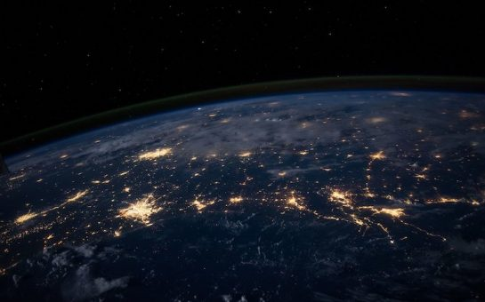 A picture of the earth from above, with a dark sky behind it. There are golden glimmers of light that connect across its surface.